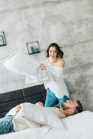 Photo for Low angle view of cheerful woman having pillow fight with handsome bearded man lying on bed - Royalty Free Image