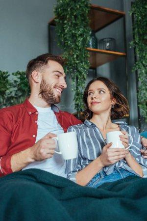 Photo pour Vue basse d'angle de l'homme gai regardant la femme attirante avec la tasse de café - image libre de droit