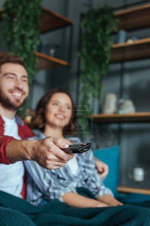 Photo pour Foyer sélectif de l'homme gai retenant le contrôleur à distance tout en regardant le film avec la femme - image libre de droit