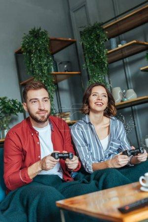 Photo pour Foyer sélectif de l'homme beau et la femme heureuse jouant la vidéo est venu dans le salon - image libre de droit