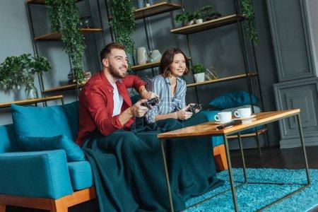 Photo pour Homme heureux et femme gaie de brunette jouant le jeu vidéo dans le salon - image libre de droit