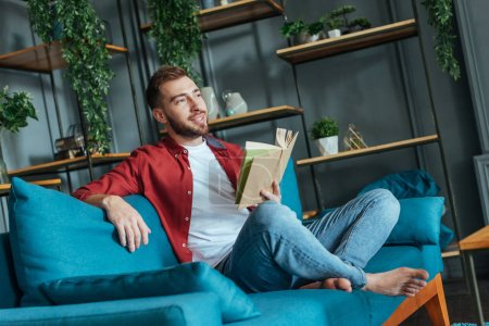 Photo for Handsome bearded man sitting on sofa and holding book in living room - Royalty Free Image