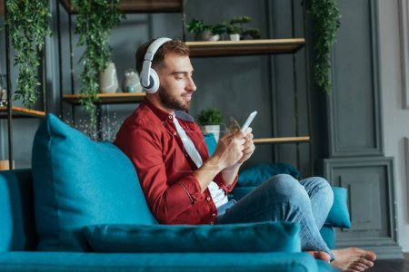 Photo for Selective focus of handsome bearded man listening music in headphones and using smartphone in living room - Royalty Free Image