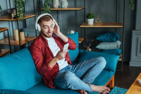 Photo for Happy bearded man listening music in headphones and using smartphone in living room - Royalty Free Image