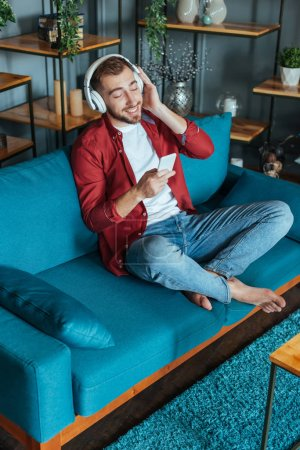 Photo for Overhead view of happy bearded man listening music in headphones and using smartphone in living room - Royalty Free Image