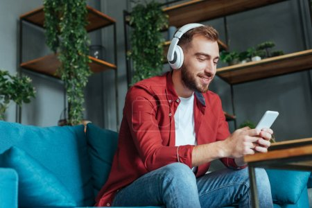Photo for Low angle view of happy bearded man listening music in headphones and using smartphone in living room - Royalty Free Image
