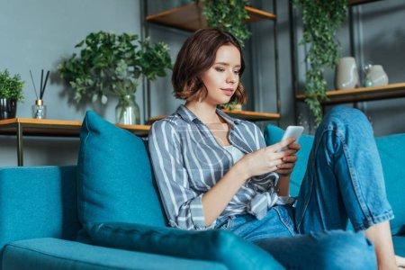 Photo pour Vue d'angle bas de la femme attirante utilisant le smartphone dans le salon - image libre de droit