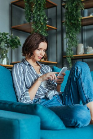 Photo for Low angle view of attractive brunette woman using smartphone in living room - Royalty Free Image