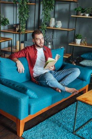 Foto de Handsome man sitting on sofa and holding book in living room - Imagen libre de derechos