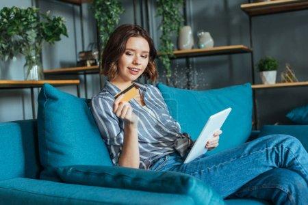 Photo pour Femme gai regardant la carte de crédit tout en retenant la tablette numérique - image libre de droit