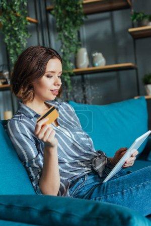 Photo pour Femme attirante regardant la tablette numérique tout en retenant la carte de crédit - image libre de droit