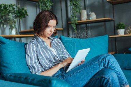Photo pour Femme attirante s'asseyant sur le sofa et utilisant la tablette numérique dans le salon - image libre de droit