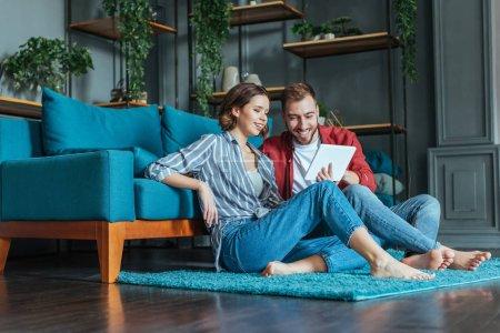 Photo pour Vue bas d'angle de l'homme et de la femme heureux regardant la tablette numérique dans le salon - image libre de droit