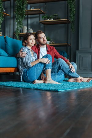 Photo for Low angle view of happy man hugging attractive woman while sitting on carpet in living room - Royalty Free Image