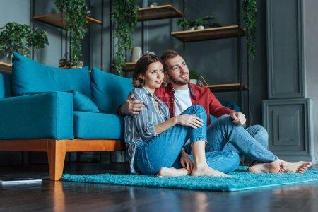 Photo pour Vue bas d'angle de l'homme gai étreignant la femme attirante tout en s'asseyant sur le tapis dans le salon - image libre de droit