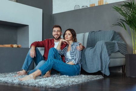Photo for Happy man smiling while sitting on carpet with beautiful brunette woman - Royalty Free Image