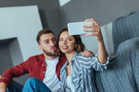 Photo pour Foyer sélectif de la femme gaie prenant le selfie sur le smartphone avec l'homme barbu - image libre de droit