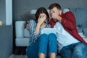 woman and man covering faces while watching video on digital tablet