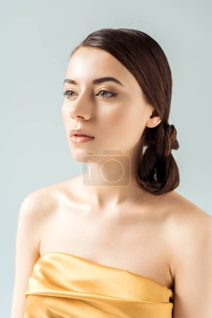 Foto de Young woman with shiny lips and golden eye shadow looking away isolated on grey - Imagen libre de derechos