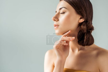 young tender woman with closed eyes, shiny lips and golden eye shadow isolated on grey