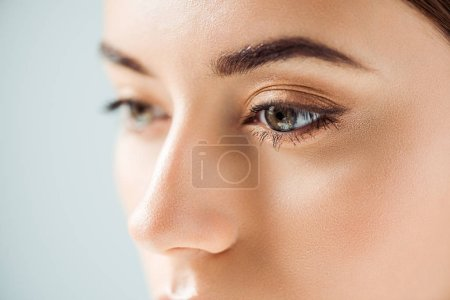 close up of young woman with golden eye shadow isolated on grey