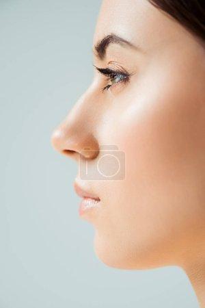 Photo pour Profil de jeune femme avec des lèvres brillantes, surligneur et ombre d'oeil d'or d'isolement sur le gris - image libre de droit