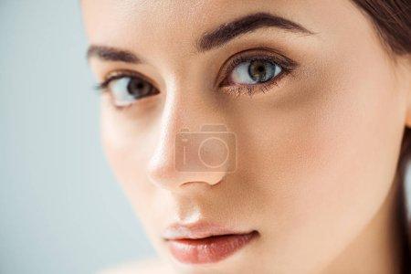 Photo pour Gros plan de jeune belle femme aux lèvres brillantes et ombre à paupières dorée isolée sur gris - image libre de droit