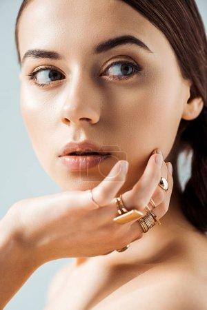 Photo for Young woman with shiny makeup and golden rings looking away isolated on grey - Royalty Free Image