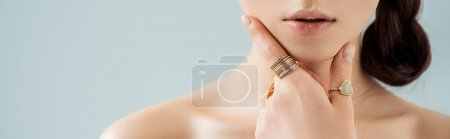 Foto de Cropped view of young woman in golden rings touching face isolated on grey - Imagen libre de derechos