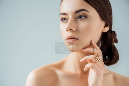Photo for Young woman with shiny makeup and golden rings touching face and looking away isolated on grey - Royalty Free Image