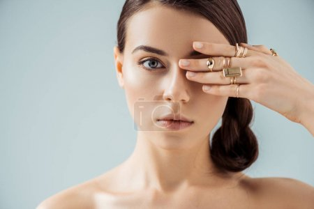 Photo for Young nude woman with shiny makeup and golden rings hiding eye behind hand isolated on grey - Royalty Free Image