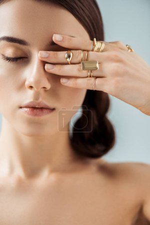 Foto de Young naked woman with shiny makeup and closed eyes in golden rings hiding eye behind hand isolated on grey - Imagen libre de derechos