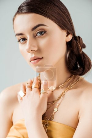 Photo pour Young attractive woman with shiny makeup in golden necklaces and rings looking at camera isolated on grey - image libre de droit