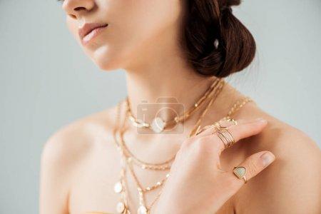 Foto de Vista recortada de la mujer joven con labios brillantes en collares de oro y anillos aislados en gris - Imagen libre de derechos