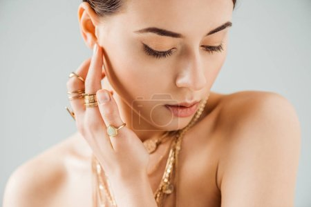 Foto de Young naked woman with shiny makeup in golden necklaces and rings isolated on grey - Imagen libre de derechos