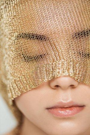 Photo pour Gros plan de jeune femme aux yeux fermés, lèvres brillantes et tissu doré sur le visage - image libre de droit