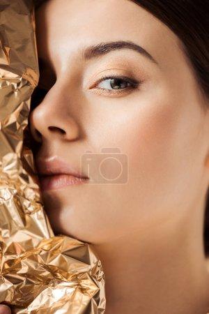Foto de Young beautiful woman with shiny makeup near golden foil looking at camera - Imagen libre de derechos