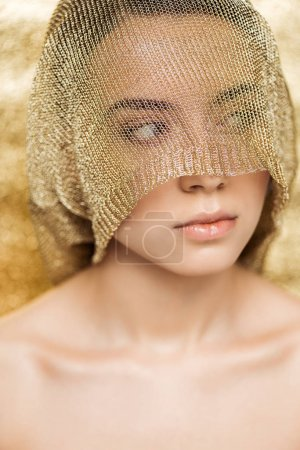 Foto de Young naked woman with shiny lips and golden cloth on face looking away on gold textured background - Imagen libre de derechos
