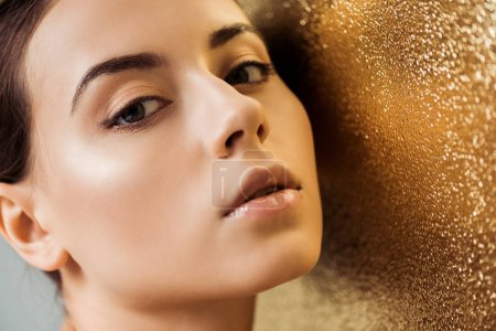 Photo for Beautiful woman with shiny makeup looking at camera on golden textured background - Royalty Free Image