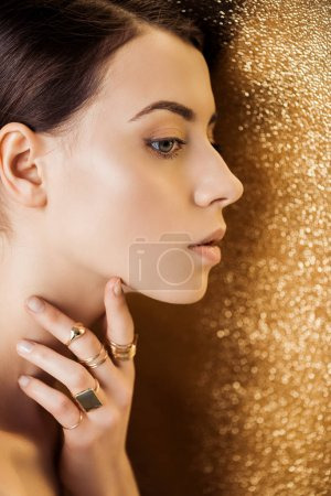 Photo for Young woman with shiny makeup and golden rings looking away on golden textured background - Royalty Free Image
