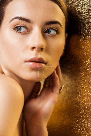 Photo for Nude attractive young woman with shiny makeup and golden rings on golden textured background - Royalty Free Image