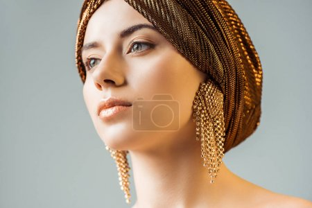 Foto de Young naked woman with shiny makeup, golden rings in turban looking away isolated on grey - Imagen libre de derechos