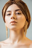 """Постер, картина, фотообои """"young naked woman with shiny makeup, golden rings in turban looking at camera isolated on grey"""""""