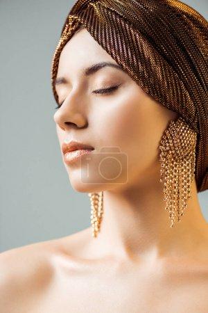 Photo pour Jeune femme nue aux yeux fermés, maquillage brillant, bagues dorées en turban isolé sur gris - image libre de droit
