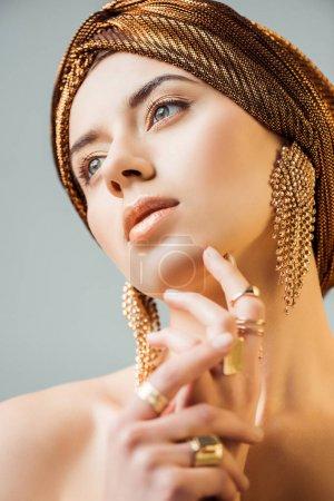Photo pour Jeune femme nue avec maquillage brillant, anneaux d'or et boucles d'oreilles en turban isolé sur gris - image libre de droit