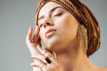 Photo pour Jeune femme nue aux yeux fermés, maquillage brillant, bagues dorées et boucles d'oreilles en turban isolé sur gris - image libre de droit