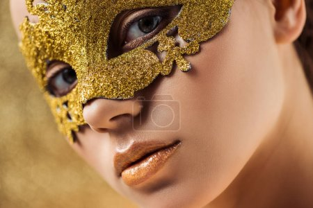 Photo pour Fermer vers le haut la vue de la jeune femme dans le masque d'or avec le maquillage brillant regardant l'appareil-photo - image libre de droit