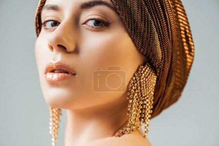 Photo pour Jeune belle femme au maquillage brillant, turban et boucles d'oreilles dorées regardant la caméra isolée sur gris - image libre de droit