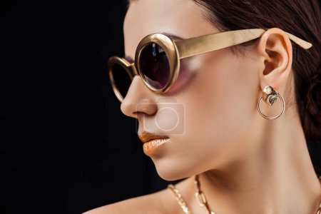 Photo pour Young nude woman in sunglasses, golden earring and necklaces isolated on black - image libre de droit
