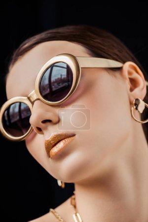 Photo pour Jeune femme en lunettes de soleil, boucle d'oreille dorée et colliers isolés sur noir - image libre de droit